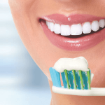 Image of a patient getting ready to brush her teeth. One dental myths is that if you only brush in the morning, your teeth are fine.