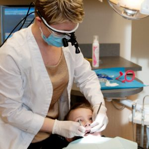dentist near me Dr. Jodi Day taking care of a child, providing dental care in Lincoln, NE