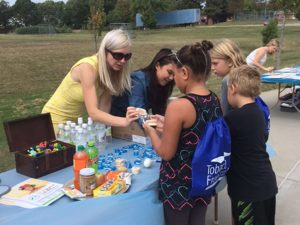 children's dentist handing out bottled water to children in Lincoln, NE Health Fair