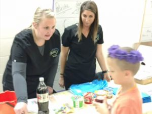 Children's Dentist Hygienists educating children at health event in Lincoln, NE